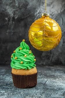 Vorderansicht mini bunte cupcakes gelb weihnachtsbaumkugel auf dunkelheit