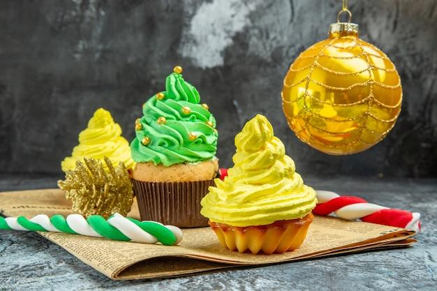 Vorderansicht mini bunte cupcakes weihnachtsbaum spielzeug weihnachtsbonbons auf zeitung auf dunklem hintergrund