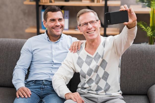 Vorderansicht mit dem vater und sohn, die ein selfie nehmen