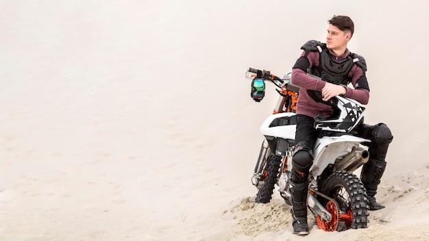 Vorderansicht motorradfahrer, der in der wüste entspannt