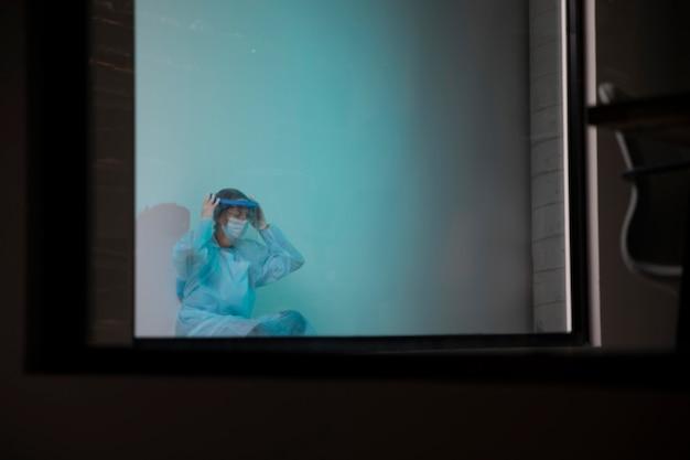 Vorderansicht müder arzt, der im krankenhaus sitzt