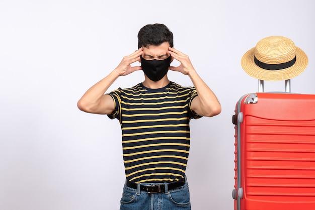 Vorderansicht müder junger tourist mit schwarzer maske, die nahe rotem koffer steht