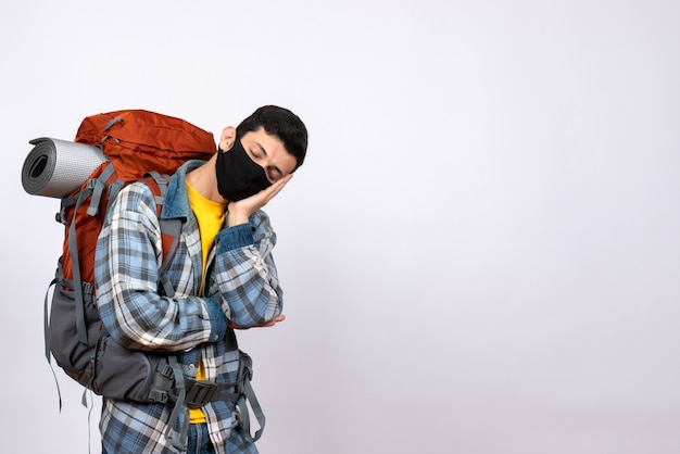 Vorderansicht müder männlicher reisender mit rucksack und maskenschlaf
