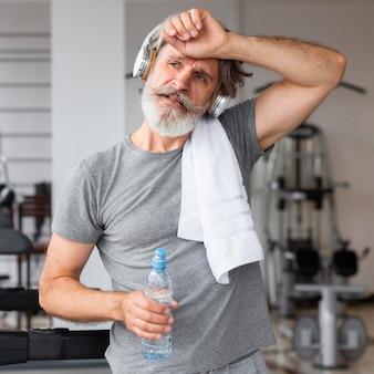 Vorderansicht müder mann im fitnessstudio