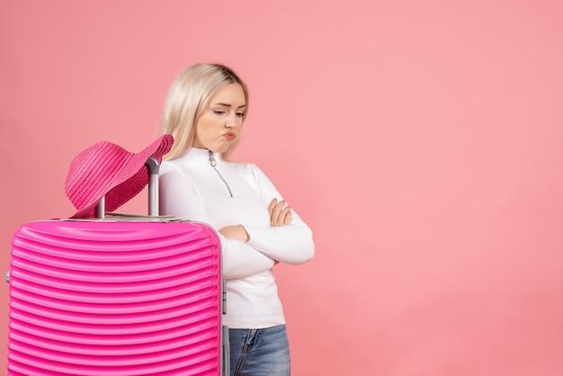 Vorderansicht mürrische blonde frau im rosa panamahut, der hände kreuzt