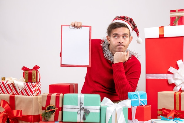 Vorderansicht nachdenklicher junger mann, der um weihnachtsgeschenke sitzt
