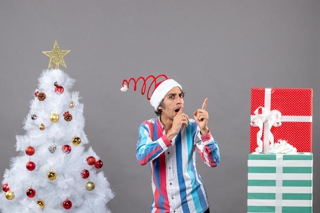 Vorderansicht nachdenklicher mann zeigen finger, die etwas zeigen, das nahe weißem weihnachtsbaum steht