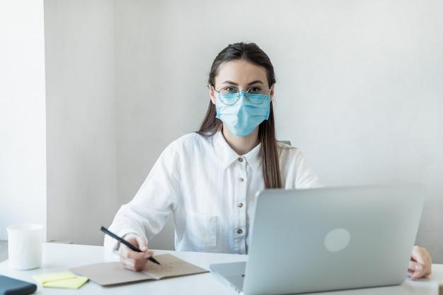 Vorderansicht nah oben von einer frau in brille medizinisches fachpersonal, das eine chirurgische maske in einem krankenhaus trägt. mitarbeiter des gesundheitswesens bei der coronavirus covid19-pandemie
