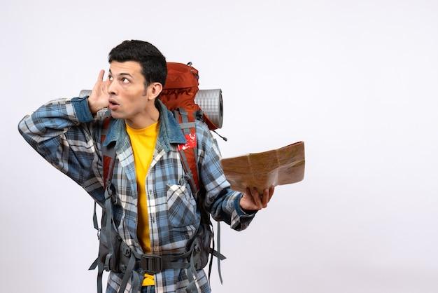 Vorderansicht neugieriger junger camper mit rucksack, der karte hält, die auf etwas hört