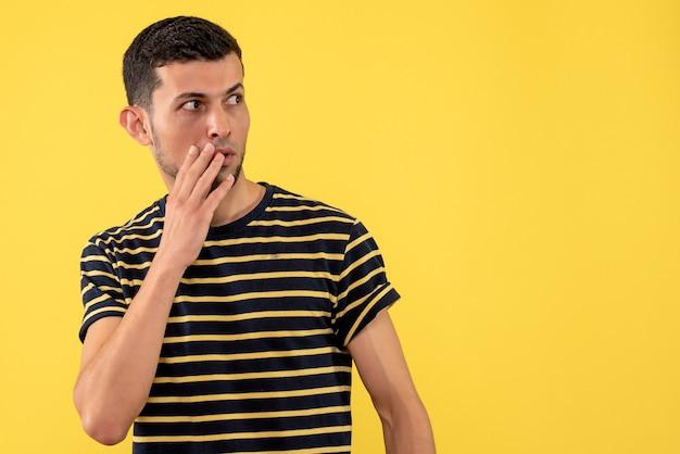 Vorderansicht neugieriger junger mann im schwarzen und weißen gestreiften t-shirt gelben isolierten hintergrund freien platz