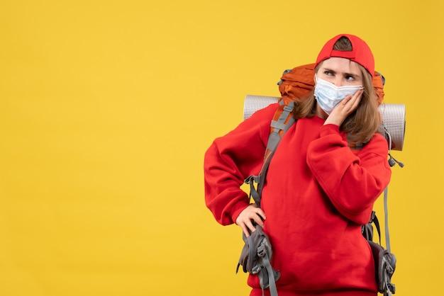 Vorderansicht neugieriger weiblicher camper mit rucksack und maske, die hand auf eine taille setzen und denken