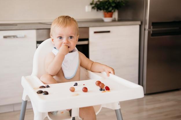 Vorderansicht niedliches baby, das allein isst