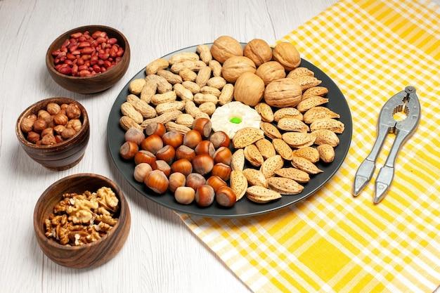 Vorderansicht nüsse zusammensetzung frische walnüsse erdnüsse und haselnüsse innerhalb der platte auf weißem schreibtisch nuss viele baum snack pflanzenschale