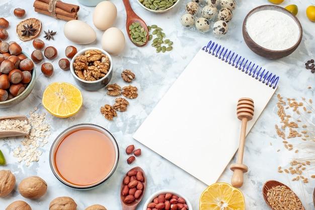 Vorderansicht offener notizblock mit eiermehlgelee verschiedene nüsse und samen auf weißem hintergrund nussteigfarbe kuchen süßer kuchen fotozucker