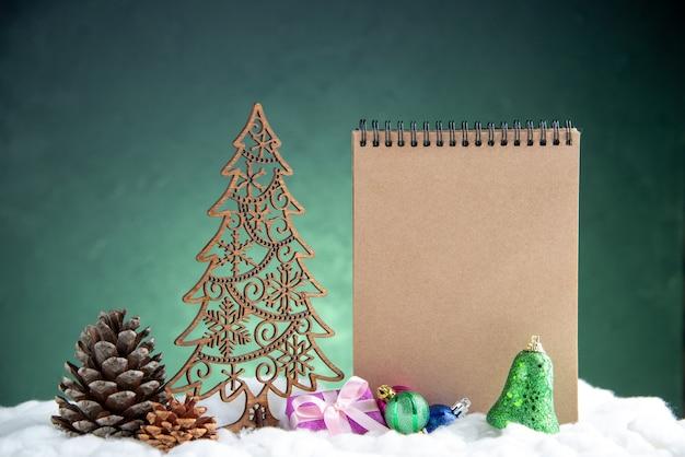 Vorderansicht offener tannenzapfen aus holz weihnachtsbaum notizblock weihnachtsbaumkugeln auf grün isolierter oberfläche