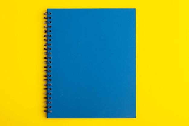 Vorderansicht offenes blaues heft auf gelbem schreibtisch