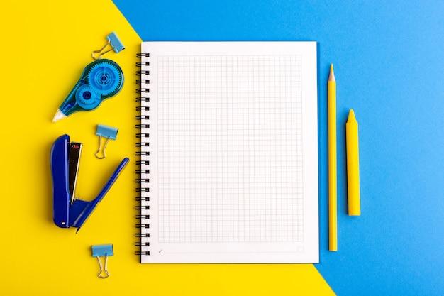 Vorderansicht offenes blaues heft mit aufklebern auf gelb-blauer oberfläche