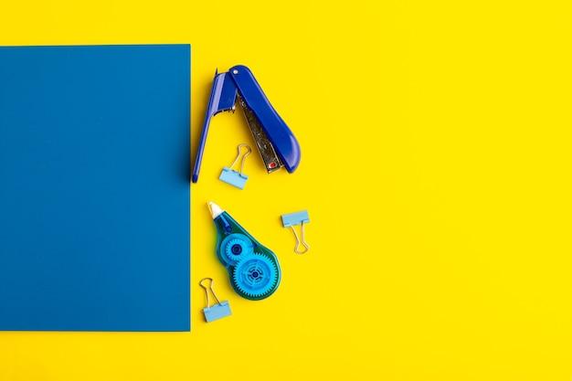 Vorderansicht offenes blaues heft mit aufklebern auf gelber oberfläche