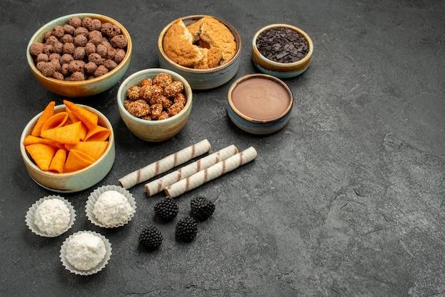 Vorderansicht orange cips mit süßen nüssen und schokoladenflocken auf einem dunkelgrauen hintergrund mahlzeit snack frühstück nuss
