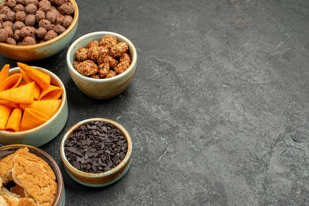 Vorderansicht orange cips mit süßen nüssen und schokoladenflocken auf grauem hintergrund mahlzeit snack frühstück nuss