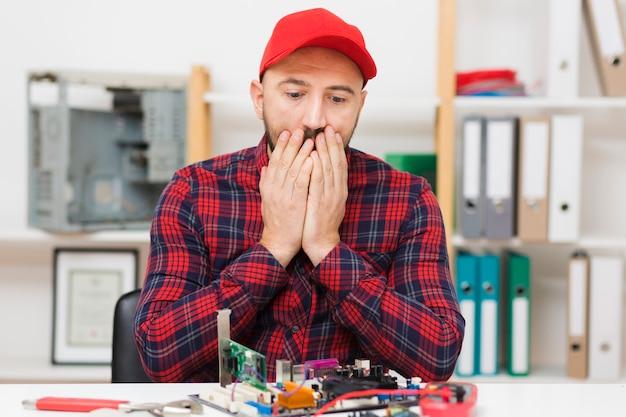 Vorderansicht person, die ein motherboard repariert