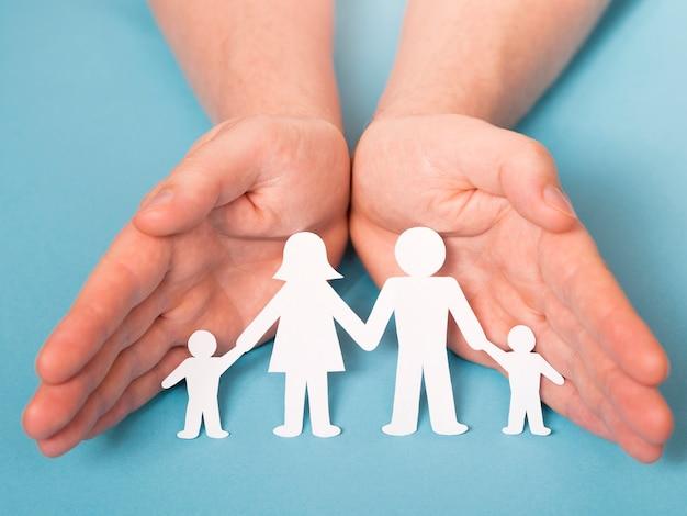 Vorderansicht person, die in händen niedliche papierfamilie hält