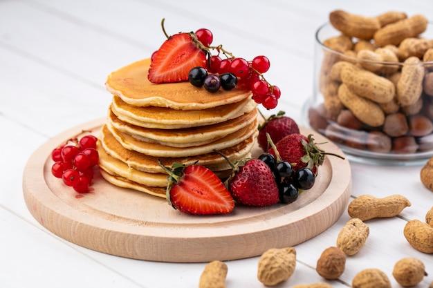 Vorderansicht pfannkuchen mit erdbeeren schwarzen und roten johannisbeeren auf einem tablett mit erdnüssen