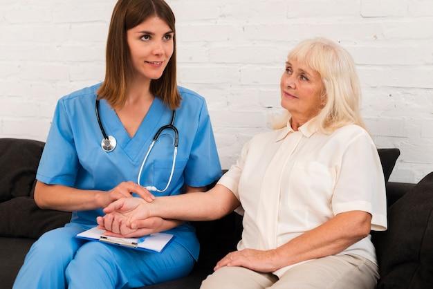 Vorderansicht-pflegekrafthändchenhalten mit alter frau