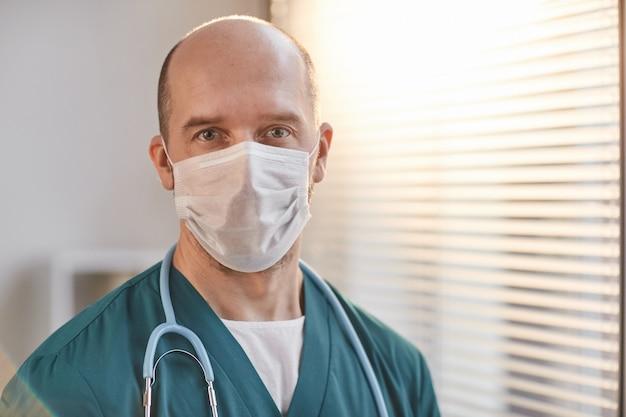 Vorderansicht-porträt eines reifen männlichen tierarztes, der maske trägt und die kamera in der tierklinik anschaut, kopierraum