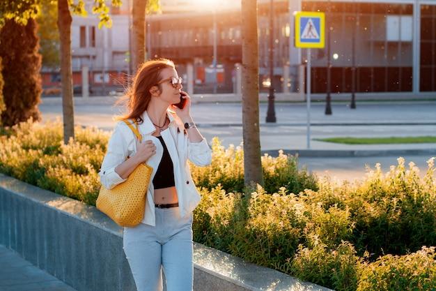 Vorderansicht porträt moderne mode glückliche frau hipster zu fuß und mit einem smartphone auf einer stadtstraße mit sonnenbrille in der sommersonne. internet, online-service, telefon, mädchen, weiblich