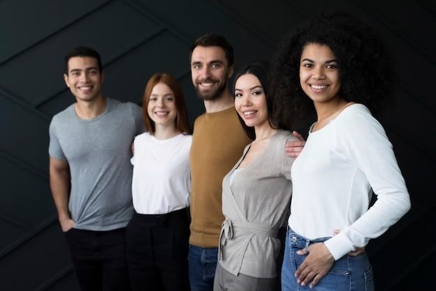 Vorderansicht positive junge leute, die zusammen aufwerfen
