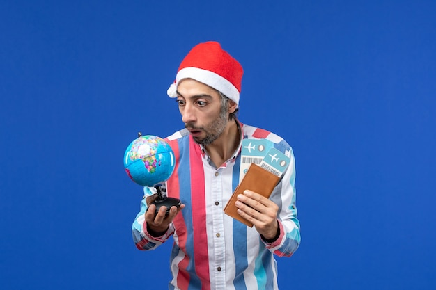 Vorderansicht regulärer mann mit eintrittskarten und globus auf neujahrsfeiertag des blauen bodens