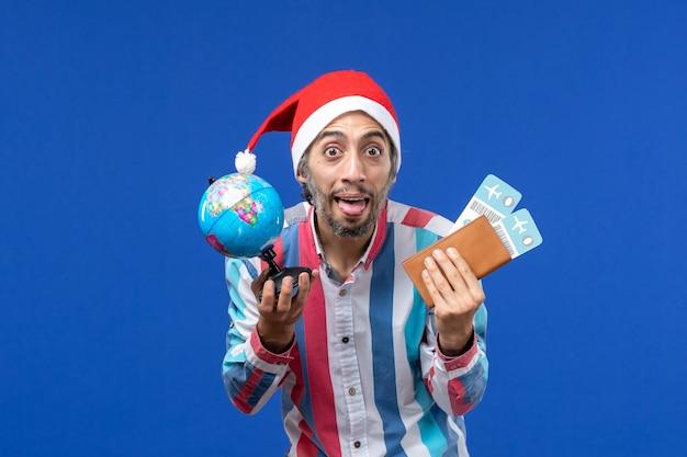 Vorderansicht regulärer mann mit globus und tickets auf dem blauen wand-emotionsfeiertags-neujahr