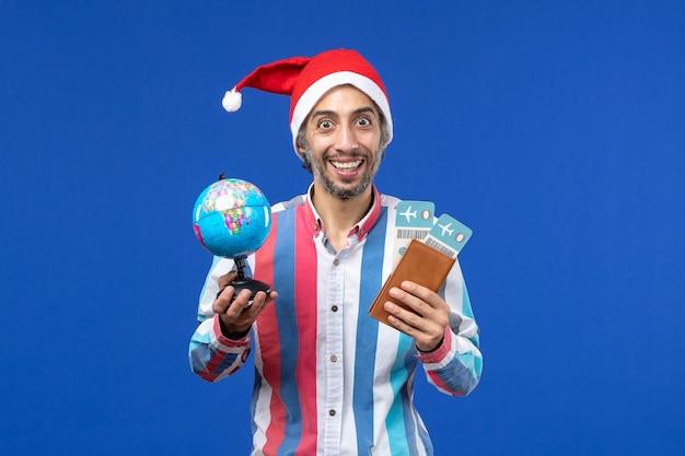 Vorderansicht regulärer mann mit tickets und globus auf einer blauen wandfeiertags-neujahrsfarbe