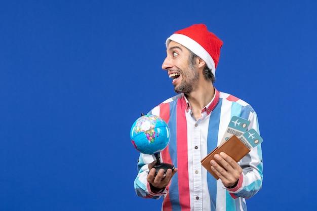 Vorderansicht regulärer mann mit tickets und globus auf einer blauen wandfeiertagsfarbe neues jahr