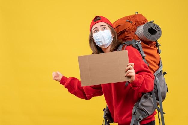 Vorderansicht reisendes mädchen mit rucksack und maske, die pappe hält, die nach hinten zeigt