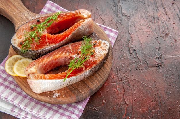 Vorderansicht rohe fischscheiben auf dunkelrotem fleisch farbfoto mahlzeit essen meeresfrüchte gericht grill