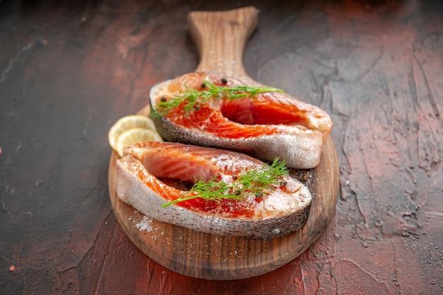 Vorderansicht rohe fischscheiben mit zitronenscheiben auf dunkelrotem grillgericht fleisch meeresfrüchtegericht mahlzeit farbfoto