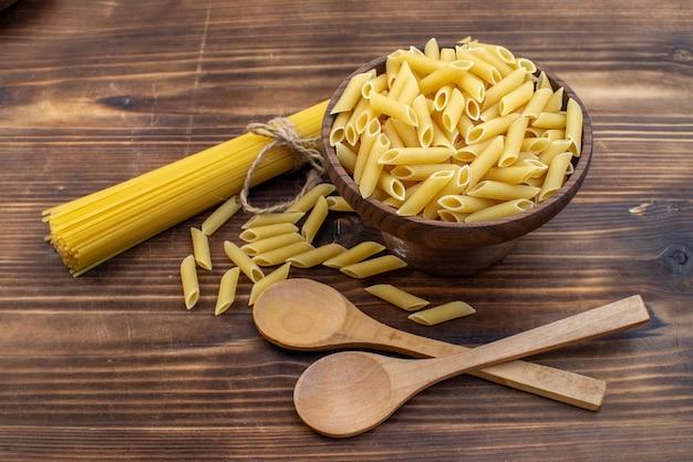 Vorderansicht rohe italienische nudeln lang und wenig geformt auf brauner oberfläche