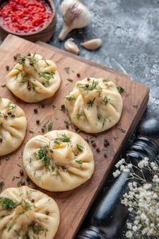 Vorderansicht rohe kleine knödel auf grauer oberfläche fleisch teig mahlzeit mahlzeit kuchen abendessen kochgericht küche