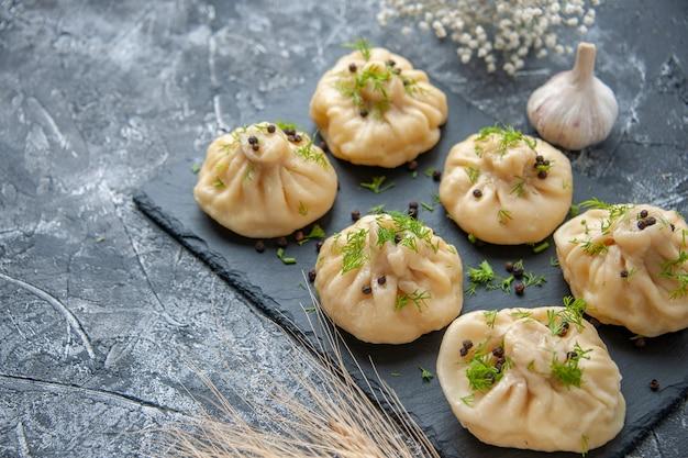 Vorderansicht rohe kleine knödel kleine teigstücke auf hellgrauer oberfläche küche kuchen gericht abendessen fleisch teig mahlzeit kochen