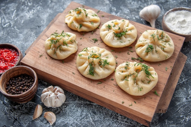 Vorderansicht rohe kleine knödel mit fleisch und tomatensauce auf grauer oberfläche teig hotcake küche mahlzeit kuchen kuchen kochen