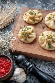 Vorderansicht rohe kleine knödel mit fleisch und tomatensauce auf grauer oberfläche teig mahlzeit kuchen torte gericht abendessen küche fleisch kochen