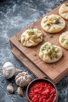 Vorderansicht rohe kleine knödel mit fleisch und tomatensauce auf grauer oberfläche teigkuchen hotcake kochküche mahlzeit kuchen