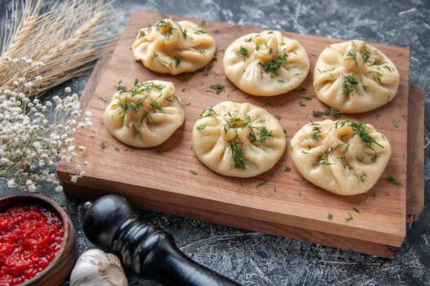 Vorderansicht rohe kleine knödel mit fleisch und tomatensauce auf hellgrauer oberfläche teig mahlzeit kuchen kuchen gericht abendessen küche fleisch kochen