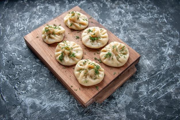 Vorderansicht rohe kleine knödel mit gemüse und fleisch innen auf grauer oberfläche teigkuchen hotcake kochküche mahlzeit kuchen
