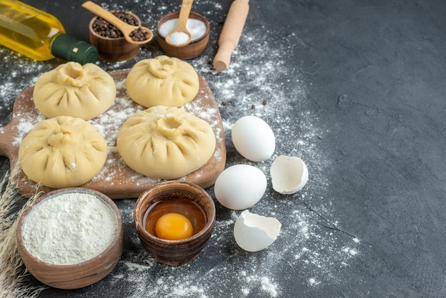 Vorderansicht rohe knödel auf schneidebrett mit mehl und eiern auf dunklem hintergrund abendessen horizontales kochen restaurant essen teig fleisch
