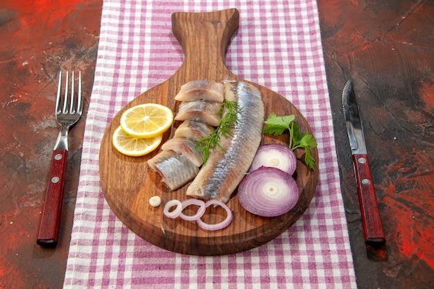 Vorderansicht roher in scheiben geschnittener fisch mit zwiebelringen und zitrone auf dunkler mahlzeit meeresfrüchte farbe salat fleisch snack gesundheit