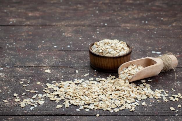 Vorderansicht rohes haferflocken hell über die dunklen cracker snack brot trockenmahlzeit nützliche gesundheit frühstück gefärbt