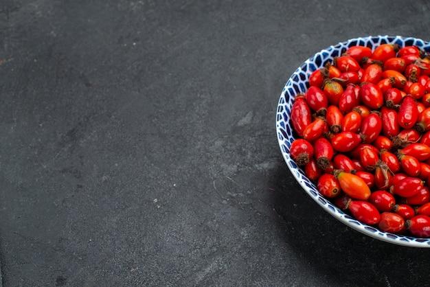 Vorderansicht rote früchte reife und saure beeren innerhalb platte auf grauer oberfläche früchte beerenfarbe vitamin baum pflanze
